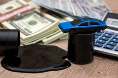 Oil pool and barrels with dollars, calculator and toy car. On the table Royalty Free Stock Photo