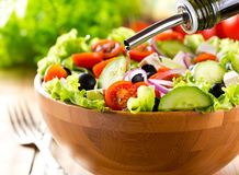 Oil pouring into bowl of vegetable salad royalty free stock photo