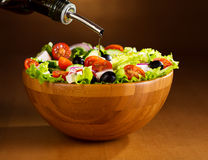 Oil pouring into bowl of vegetable salad Royalty Free Stock Images