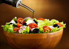 Oil pouring into bowl of vegetable salad Stock Images