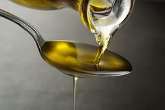 Bottle of oil pouring to the spoon close up Stock Image