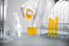 Young Asian scientist with test tube making research in clinical laboratory.Science, chemistry, technology, biology and people con. Oil pouring, Formulating the Stock Images