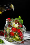 Oil pouring in a mason jar with fresh vegetables on dark backgro. Oil pouring in a mason jar with fresh vegetables Royalty Free Stock Photography
