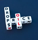 Oil price drops. Text 'oil price drops' inscribed in uppercase letters on small white cubes and arranged jigsaw style, dark background Royalty Free Stock Image
