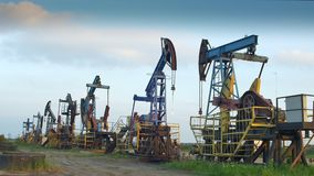 Oil Producing Rigs in Perspective. Continuously working oil pumps extracting raw materials stock video footage