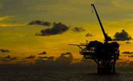 Oil production rig. Into the sea on sunset Royalty Free Stock Photography