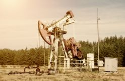 Oil production, oil well stands on the field among the forest, blue sky, extraction of petroleum, industrial, machine, toned royalty free stock photo