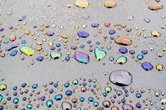 Oil products got into the water and on the surface of water droplets formed patterns. Of color stock photos