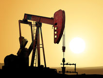 Oil pump. Working oil pump in deserted district at sunset Royalty Free Stock Image