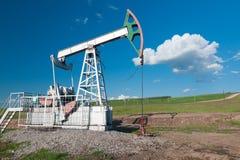 Oil pump. On a green field Stock Photos