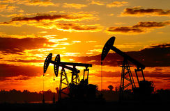 Oil pump. Silhouette against a bright orange sky Stock Photography