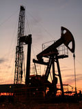 Oil pump. Silhouette of swinging oil pump in evening sky Stock Photography