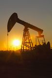 Oil pump against setting sun Royalty Free Stock Photos