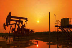Oil pump against setting sun Stock Photography