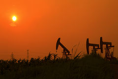 Oil pump against setting sun Stock Image