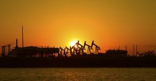 Oil pump against setting sun Stock Images