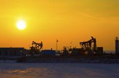 Oil pump against setting sun Stock Photos