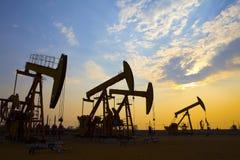 Oil pump against setting sun stock photography