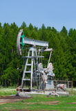 Oil pump. On a background the forest Stock Photos