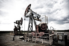 Oil pump in the field. Oil pums in the fields cold contrast giving techno mood against dramatic cloudscape Royalty Free Stock Photo