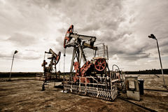 Oil pump in the field. Oil pums in the fields vintage rusty colour against moody cloudscape Royalty Free Stock Photography