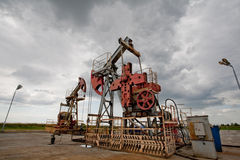 Oil pump in the field. Oil pums in the fields against moody cloudscape Royalty Free Stock Images