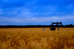 Oil pump in field. An oil pump working in a field of wheat before a storm Royalty Free Stock Image