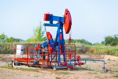 The oil pump, industrial equipment. Oil field site, oil pumps are running. Rocking machines for oil production in a stock photos
