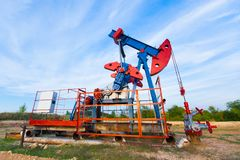 The oil pump, industrial equipment. Oil field site, oil pumps are running. Rocking machines for oil production in a royalty free stock photo