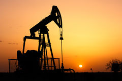 The oil pump. Oil pump, industrial machine for petroleum in the sunset background Royalty Free Stock Photo