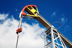 Oil pump jack. Against blue sky background Royalty Free Stock Photos
