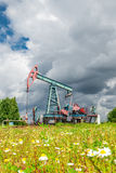 Oil pump jack in a field of chamomile flowers under dark cloudy skies Royalty Free Stock Images
