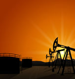 Oil pump jack for petroleum and reserve tanks on sunrise backgro Royalty Free Stock Photo