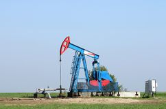 Oil pump jack and pipeline. On field stock photos