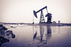 Oil pump jack and reflection. Toned color Royalty Free Stock Image
