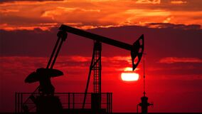 Oil pump jack against red sunset. Oil pump jack silhouette against bloody red sunset stock video footage