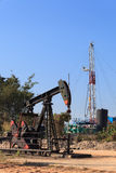 Oil Pump Jack (Sucker Rod Beam) and Drilling Rig. On Sunny Day Royalty Free Stock Photography