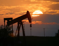 Oil pump jack at sunset Stock Images