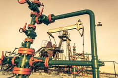 Oil pump jack and wellhead on an oil field. Mining and petroleum industry. Power generation concept. Oil and gas industry theme royalty free stock images