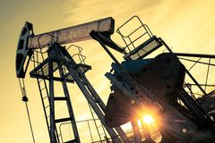 Oil pump jack and wellhead on an oil field. Mining and petroleum industry. Power generation concept. Oil and gas industry theme royalty free stock photo