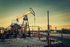 Oil pump jack and wellhead on an oil field. Mining and petroleum industry. Power generation concept. royalty free stock photos