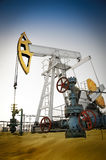 Oil pump jack and wellhead in the oilfield Stock Images