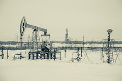 Oil pump jack and wellhead in the oilfield Stock Photo