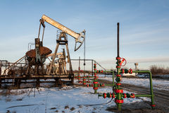 Oil pump jack and wellhead in the oilfield Stock Photography