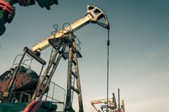 Oil pump jack and wellhead in the oilfield Royalty Free Stock Photography