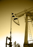 Oil pump jack and wellhead in the oilfield Royalty Free Stock Images
