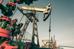 Oil pump jack and wellhead in the oilfield Stock Photos