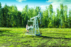 Oil pump / Oil pump on chink in the field Stock Photography