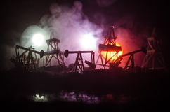 Oil pump oil rig energy industrial machine for petroleum, Group oil rigs and brightly lit industrial site at night. Toned.Backgrou. Nd for design. Selective Stock Photography