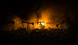 Oil pump oil rig energy industrial machine for petroleum, Group oil rigs and brightly lit industrial site at night. Toned.Backgrou. Nd for design. Selective Royalty Free Stock Image